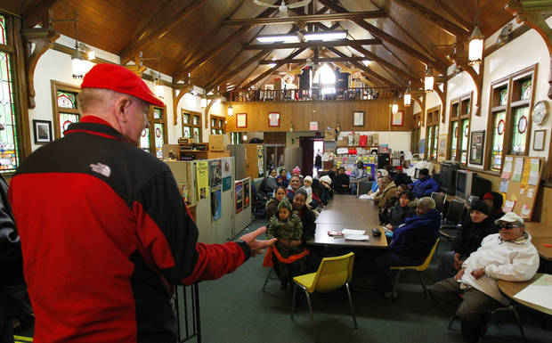 A wealthy philanthropist from Kansas City, Mo., known as Secret Santa, distributes $100 dollar bills to needy people at St. Joseph's Social Service Center in Elizabeth, N.J., Thursday, Nov. 29, 2012. (AP Photo/Rich Schultz)