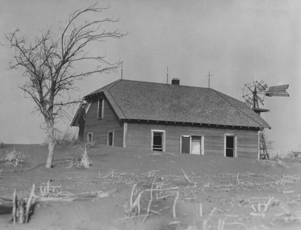 Soil piles up in an abandoned farm house during the dust storms of 1936.