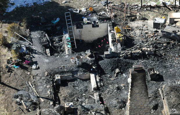 In this aerial photo, law enforcement authorities investigate the burnt-out cabin Wednesday, Feb.13, 2013, where quadruple-murder suspect Christopher Dorner is believed to have died after barricading himself inside during a Tuesday stand-off with police in the Angeles Oaks area of Big Bear, Calif. San Bernardino Sheriff's Deputy Jeremiah MacKay was killed and another wounded during the shootout with Dorner. (AP Photo/The Sun, John Valenzuela)