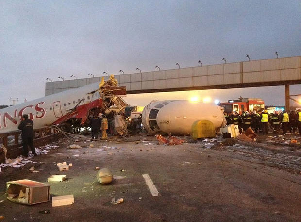 Rescuers work at the site of careered off the runway plane at Vnukovo Airport in Moscow, Saturday, Dec. 29, 2012. A Tu-204 aircraft belonging to Russian airline Red Wings careered off the runway at Russia&#039;s third-busiest airport on Saturday, broke into pieces and caught fire, killing several people. (AP Photo/Alexander Usoltsev)