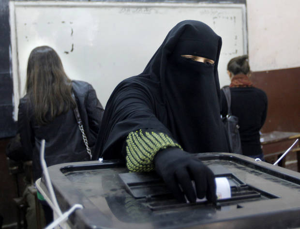 An Egyptian woman casts her vote at a polling station during a referendum on a disputed constitution drafted by Islamist supporters of President Morsi in Cairo, Egypt, Saturday, Dec. 15, 2012. Egyptians were voting on Saturday on a proposed constitution that has polarized their nation, with Morsi and his Islamist supporters backing the charter, while liberals, moderate Muslims and Christians oppose it. (AP Photo/Amr Nabil)