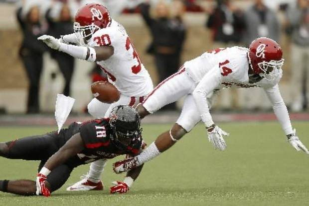 Oklahoma's Javon Harris (30) and Aaron Colvin (14) break up a pass intended for Texas Tech's Eric Ward (18). Photo by Bryan Terry, The Oklahoman
