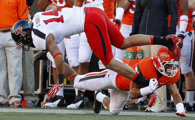 Oklahoma State's Ashton Lampkin (6) brings down Texas Tech's Darrin Moore (14) during a college football game between Oklahoma State University (OSU) and Texas Tech University (TTU) at Boone Pickens Stadium in Stillwater, Okla., Saturday, Nov. 17, 2012.  Photo by Bryan Terry, The Oklahoman