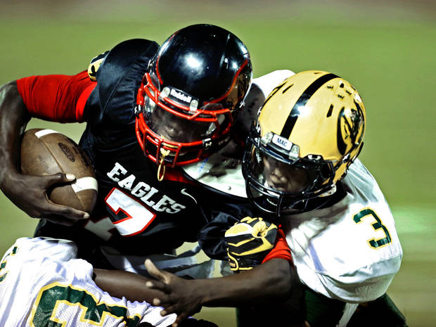Del City's Terry Wilson carries the ball late in the second quarter and is tackled by Lawton MacArthur's Lorenzo West during a high school football game between the Lawton MacArthur Highlanders and the Del City Eagles on Friday, Sept. 27, 2013 in Del City, Okla. Photo by Steve Sisney, The Oklahoman