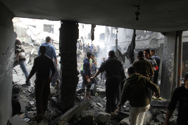 Palestinians stand in the rubble of the Daloo family house following an Israeli air strike in Gaza City, Sunday, Nov. 18, 2012. Palestinian medical officials say at least 10 civilians, including women and young children, have been killed in an Israeli airstrike in Gaza City. (AP Photo/Hatem Moussa)