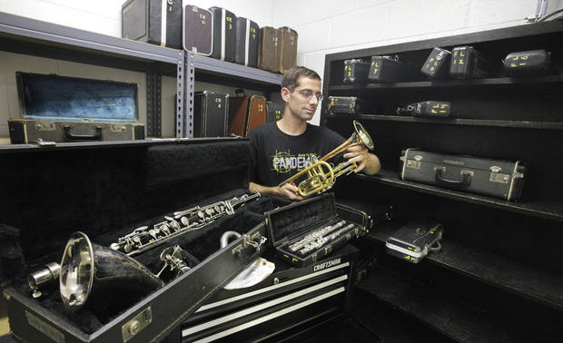 Band director Scott Filleman sorts through instruments in need of repair work that are used in the band program at Santa Fe South Schools in Oklahoma City.