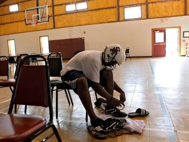 HIGH SCHOOL FOOTBALL: Marcus Smith sits in the basketball gym to change into his cleats before football practice at Seeworth Academy  in Oklahoma City on Wednesday, August 25, 2010. Photo by John Clanton, The Oklahoman ORG XMIT: KOD