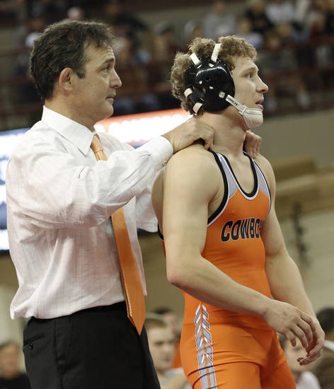 OSU head coach John Smith warms up Tyler Dorrell during the wrestling match between Oklahoma University and Oklahoma State University at McCasland Field House in Norman, Okla.,Sunday, Dec. 9, 2012.  Photo by Garett Fisbeck, For The Oklahoman