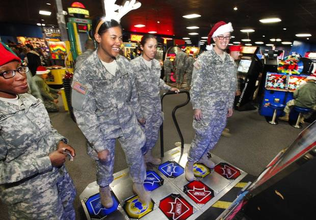 New recruits Pvt2 Nadaira Thomas and Hillary Bayne play a dance game during a lunch stop at Gatti Town during Soldiers Day Out, Friday, December 21, 2012. Edmond/North OKC Blue Star Mothers will be taking the soldiers who can't go home for Christmas around the metro for a day of fun. Photo By David McDaniel/The Oklahoman