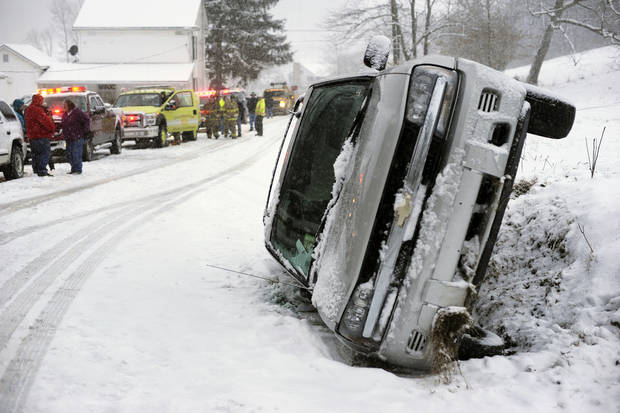 A Chevrolet Blazer went into a ditch and rolled onto its passenger side on a snow-covered Cherry Street in Rockefeller Township, Northumberland County, Pa. on Monday, March 18, 2013.  A mother and daughter escaped injury State police at Stonington did not provide any additional information. (AP Photo/The News-Item, Larry Deklinski)