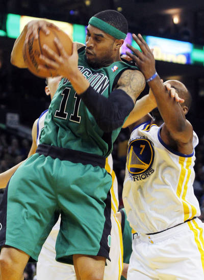 Boston Celtics' Courtney Lee, front, rebounds in front of Golden State Warriors' Andris Biedrins, behind left and Carl Landry, during the first half of an NBA basketball game in Oakland, Calif., Saturday, Dec. 29, 2012. (AP Photo/George Nikitin)