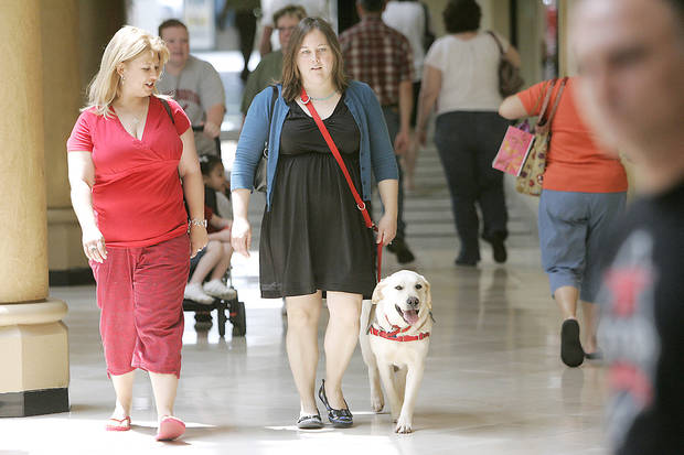 Jeanne Neugebauer, a volunteer with A New Leash on Life, and Carrie Coppernoll walk Tom in Penn Square Mall. Tom is in training to become an assistance dog. PHOTO BY STEVE GOOCH, THE OKLAHOMAN