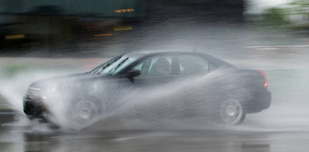Cars go through standing water on Classen Boulevard near The Curve shopping center Monday. <strong>DOUG HOKE - THE OKLAHOMAN</strong>