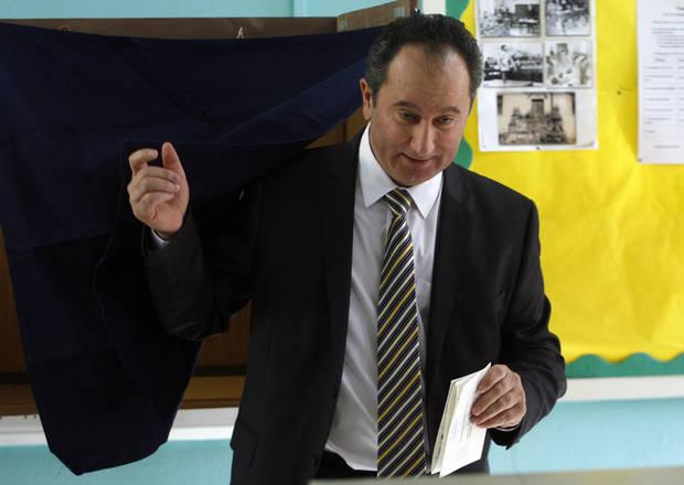 Left-wing presidential candidate Stavros Malas laves a polling booth after voting in the Presidential election in capital Nicosia, Cyprus, Sunday, Feb. 17, 2013. Cypriots are voting for a new president amid a financial crisis in which the country needs a rescue package from international creditors to stave off bankruptcy. (AP Photo/Philippos Christou)