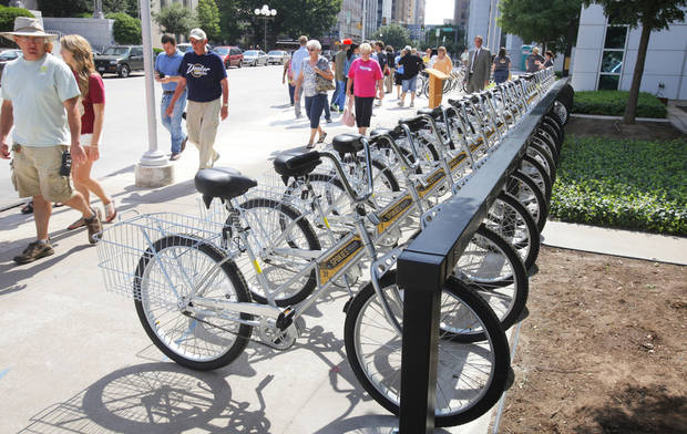 Pedestrians walk past a rack of Spokies bicycles on Friday in front of the Ronald J. Norick Downtown Library in Oklahoma City. Photo by Paul B. Southerland, The Oklahoman