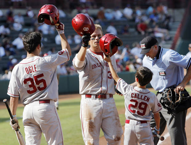 OU's Garrett Buechele, middle, is met at home plate by teammate Tyler Ogle, left, and bat boy Callen Golloway after Buechele hit a home run in the fourth inning during the Big 12 baseball championship tournament game between Kansas State and Oklahoma at the Bricktown Ballpark in Oklahoma City, Saturday, May 29, 2010. At right is umpire Patrick Spieler. OU won, 13-2, in eight innings. Photo by Nate Billings, The Oklahoman