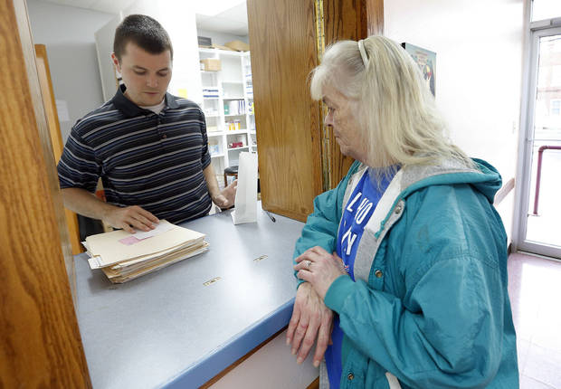 Brett Whitehead helps Katie Wedemeyer with her medications at the Good Shepherd Ministries' free clinic in Oklahoma City. Photo by Sarah Phipps, The Oklahoman  <strong>SARAH PHIPPS - SARAH PHIPPS</strong>