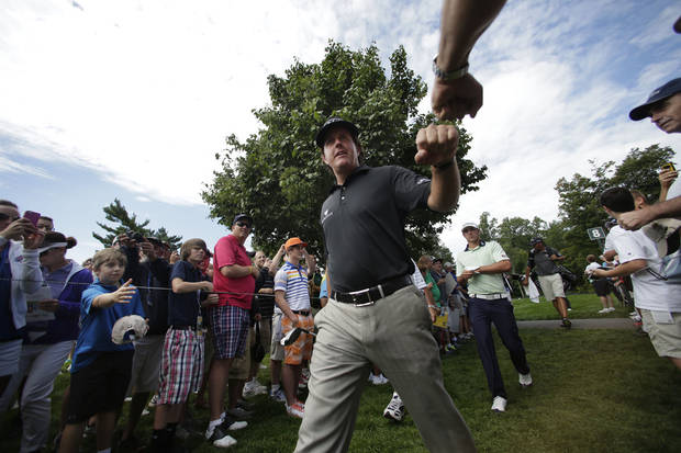Phil Mickelson taps fists with a fan as he walks to the ninth tee during a practice round for the PGA Championship golf tournament at Oak Hill Country Club, Tuesday, Aug. 6, 2013, in Pittsford, N.Y. (AP Photo/Charles Riedel)