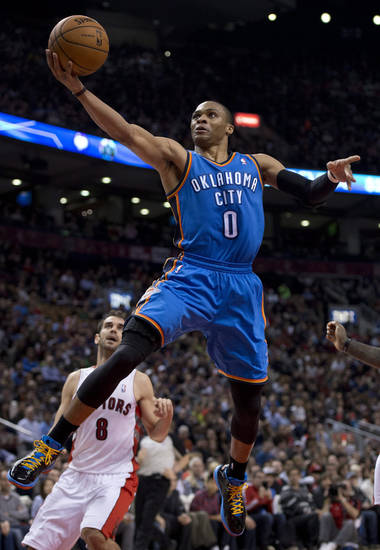 Toronto Raptors guard Jose Calderon (8) watches as Oklahoma City Thunder guard Russell Westbrook jumps to the hoop during first-quarter NBA basketball game action in Toronto, Sunday, Jan.6, 2013. (AP Photo/The Canadian Press, Frank Gunn) ORG XMIT: FNG106