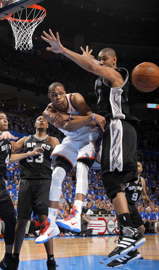 Oklahoma City's Russell Westbrook (0) passes the ball around San Antonio's Tim Duncan (21) during Game 3 of the Western Conference Finals between the Oklahoma City Thunder and the San Antonio Spurs in the NBA playoffs at the Chesapeake Energy Arena in Oklahoma City, Thursday, May 31, 2012.  Photo by Sarah Phipps, The Oklahoman