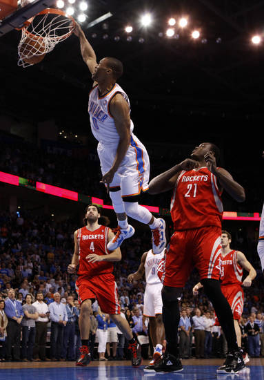 Oklahoma City's Russell Westbrook (0) dunks in front of Houston's Luis Scola (4) and Samuel Dalembert (21) during the NBA basketball game between the Oklahoma City Thunder and the Houston Rockets at the Chesapeake Energy Arena, Tuesday, March 13, 2012. Photo by Sarah Phipps, The Oklahoman.