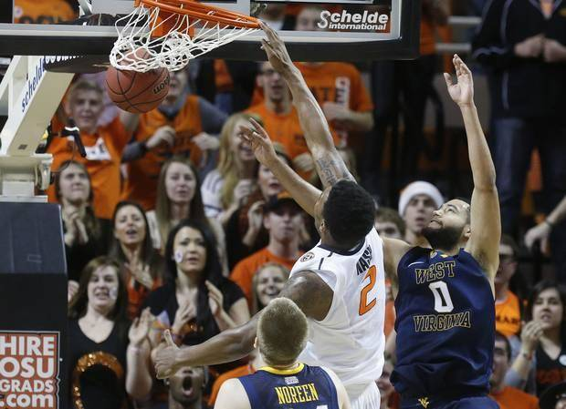 Oklahoma State junior Le'Bryan Nash (2) dunks in front of West Virginia forward Kevin Noreen (34) and forward Remi Dibo (0) in the first half of an NCAA college basketball game in Stillwater, Okla., Saturday, Jan. 25, 2014. Oklahoma State won 81-75.(AP)