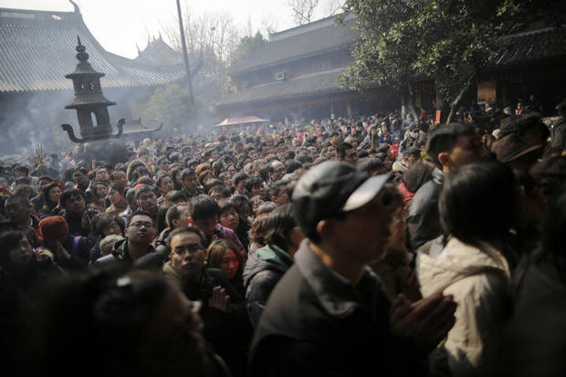 Worshippers gather to pray at Longhua Temple on the first day of the Lunar New Year,  in Shanghai, China on Sunday, Feb. 10, 2013. Millions across China are celebrating the arrival of the Lunar New Year, the Year of the Snake, marked with a week-long Spring Festival holiday.  (AP Photo/Eugene Hoshiko)