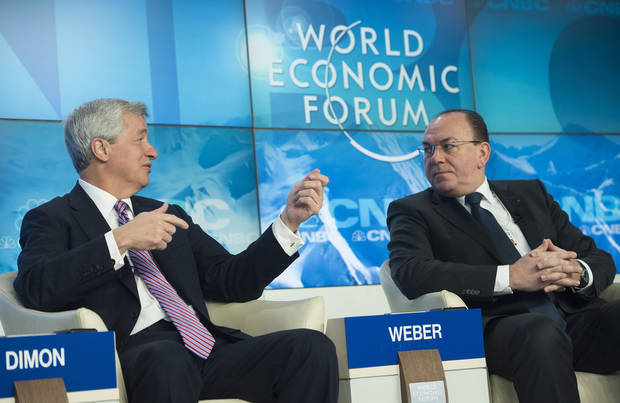 James Dimon, Chairman and Chief Executive Officer JP Morgan Chase and Co, left, and Axel A. Weber, Chairman of the Board of Directors UBS, right, gestures during a panel session on the first day of the 43rd Annual Meeting of the World Economic Forum, WEF, in Davos, Switzerland, Wednesday, Jan. 23, 2013.  (AP Photo/Keystone, Jean-Christophe Bott)