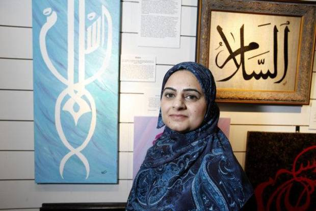 Tehmina Cheema poses with Islamic art displayed at the Midwest City Library. Cheema is an art teacher at the Muslim Mercy School in Oklahoma City.
