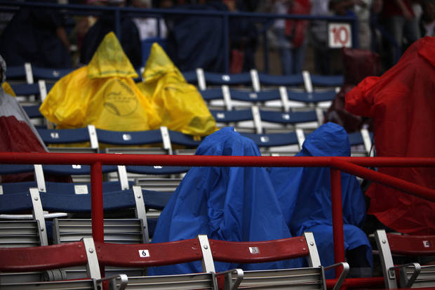 Fans hide from the rain at ASA Hall of Fame Stadium in Oklahoma City, Wednesday, June 6, 2012.  The final game of the Women's World College Series was delayed due to weather conditions.  Photo by Garett Fisbeck, The Oklahoman