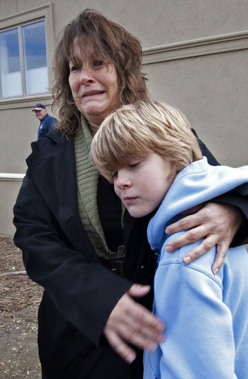 Sharon Thompson hugs her son, Justin Thompson, 9, as she cries looking at her family's ruined furniture and the boat that landed on their lawn on Nov. 1, 2012 in Brigantine, N.J. Frustration is setting in for some New Jersey residents who are still without power and running low on food. Some residents say too much attention is being paid to the Shore and not enough to working people who are hurting. (AP Photo/Philadelphia Inquirer, April Saul)