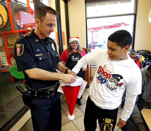 Camdyn Braden, 10, draws the badge number of his escort from a hat held by David Dickinson during the Second Annual Shop with a Cop on Saturday, Dec. 8, 2012 in Moore, Okla. Photo by Steve Sisney, The Oklahoman