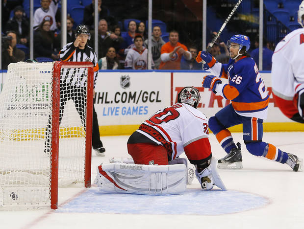 New York Islanders left wing Matt Moulson (26) celebrates scoring a goal past Carolina Hurricanes goalie Cam Ward (30) during the second period of an NHL hockey game at the Nassau Coliseum in Uniondale, N.Y., Monday, Feb.11, 2013. (AP Photo/Paul J. Bereswill)