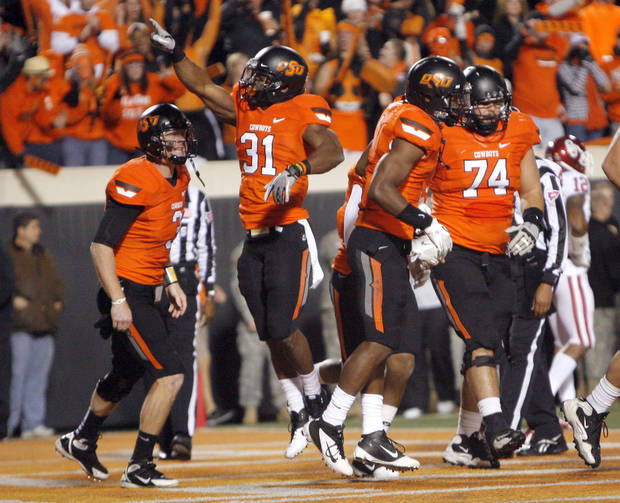 Oklahoma State&#039;s Jeremy Smith (31) celebrates a touchdown during the Bedlam college football game between the Oklahoma State University Cowboys (OSU) and the University of Oklahoma Sooners (OU) at Boone Pickens Stadium in Stillwater, Okla., Saturday, Dec. 3, 2011. Photo by Sarah Phipps, The Oklahoman