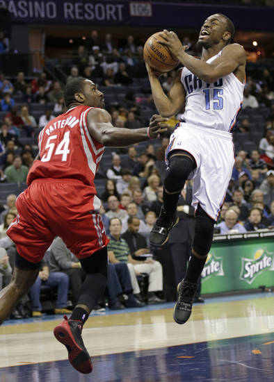 Charlotte Bobcats' Kemba Walker (15) drives past Houston Rockets' Patrick Patterson (54) during the first half of an NBA basketball game in Charlotte, N.C., Monday, Jan. 21, 2013. (AP Photo/Chuck Burton)