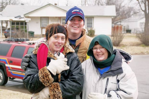 Crystal Jacobo holds Alex Jr. after his rescue by the  Midwest City Fire Department. With her are firefighter Joel Bain and neighbor Lauri Goff.  PHOTO PROVIDED  BY THE MIDWEST CITY FIRE DEPARTMENT