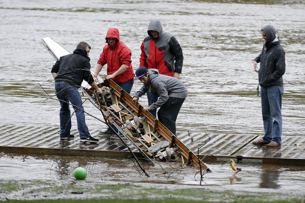 Members of the Saint Joseph's University crew team pull a damaged boat from the Schuylkill river in the wake of superstorm Sandy, Tuesday, Oct. 30, 2012, in Philadelphia. A one-two punch of rain and high wind from a monster hybrid storm that started out as a hurricane battered Pennsylvania, leaving more than a million customers without power as officials began assessing the damage Tuesday.  (AP Photo/Matt Slocum) ORG XMIT: PAMS104