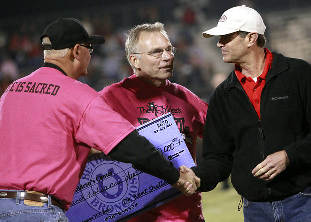 Bethany Superintendent Kent Shellenberger, left, and Washington Superintendent A.J. Brewer, right, shake hands as they present Albert Gray, CEO of The Children's Center, with a check during halftime of their high school football game in Bethany, Okla., on Friday, September 16, 2011. Photo by John Clanton, The Oklahoman