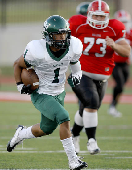 Edmond Santa Fe's Phillip Sumpter runs past Yukon's Sheldon Kearby during a high school football game in Yukon, Okla., Friday, Sept. 9, 2011. Photo by Bryan Terry, The Oklahoman