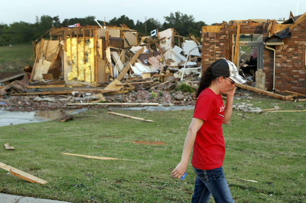 Ann Powell calls her insurance company while standing in front of what is left of her house at 306 Mounds, just south of Harrah Road and Reno Monday evening after tornados ripped through the area. Powell moved to Oklahoma about a year ago from California. Photo by Hugh Scott, The Oklahoman