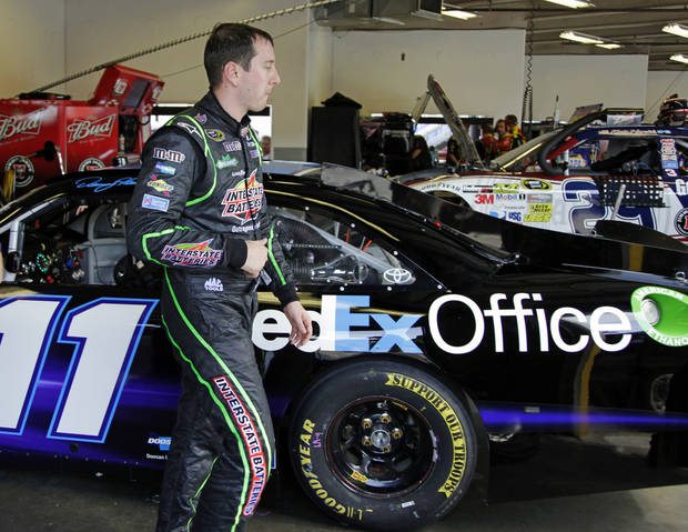 Kyle Busch leaves Denny Hamlin's garage after he drove Hamlin's car in practice for the NASCAR Sprint Cup Series Coke Zero 400 auto race at Daytona International Speedway, Thursday, July 5, 2012, in Daytona Beach, Fla. Hamlin was unable to practice because of an injury. (AP Photo/Terry Renna)