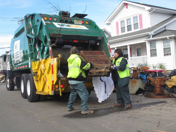   Sanitation workers collect some of the tons of ruined household items from homes in Point Pleasant Beach N.J. on Monday, Nov. 5, 2012. A new storm due Wednesday was raising fears of renewed flooding and damage at the Jersey shore, which was devastated by Superstorm Sandy. (AP Photo/Wayne Parry)  