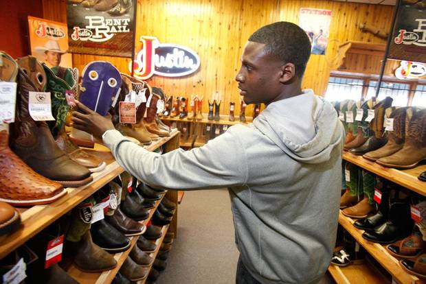 Jim Thorpe Award winner Morris Claiborne looks for a pair of boots at Tener's Western Outfitters in Oklahoma City, Monday, February  6, 2012. Tener's gives the recipient of the Jim Thorpe Award a pair of cowboy boots and hat each year. Photo By Steve Gooch, The Oklahoman