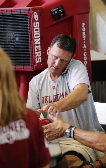 Director of recruiting Cale Gundy multi-tasks during the Meet the Sooners event inside Gaylord Family/Oklahoma Memorial Stadium at the University of Oklahoma on Saturday, Aug. 4, 2012, in Norman, Okla.  Photo by Steve Sisney, The Oklahoman