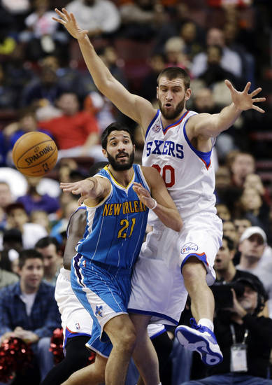New Orleans Hornets' Greivis Vasquez (21) passes the ball as Philadelphia 76ers' Spencer Hawes defends during the first half of an NBA basketball game, Tuesday, Jan. 15, 2013, in Philadelphia. (AP Photo/Matt Slocum)