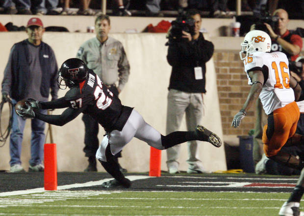 Edward Britton scores defended by Perrish Cox during the first half of the college football game between the Oklahoma State University Cowboys (OSU) and the Texas Tech Red Raiders at Jones AT&T Stadium on Saturday, Nov. 8, 2008, in Lubbock, Tex.