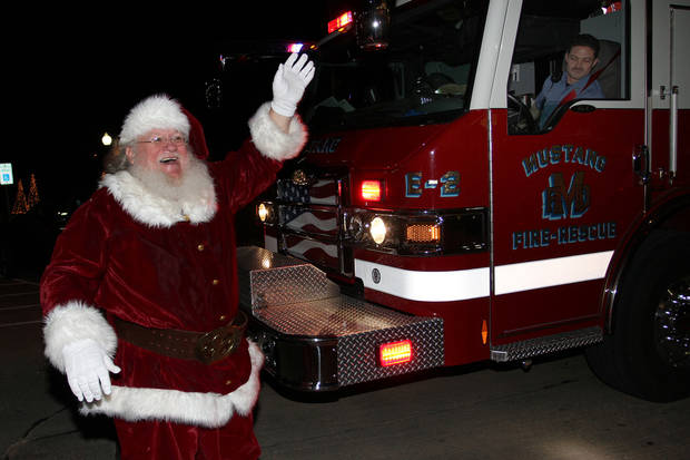 The Mustang Fire Department gave Santa Claus a ride during the community tree lighting ceremony at the Mustang Town Center Monday night. PHOTO BY HUGH SCOTT, FOR THE OKLAHOMAN