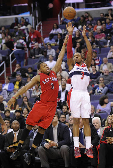 Washington Wizards guard Bradley Beal, right, takes a shot against Toronto Raptors guard Kyle Lowry, left, during the second half of an NBA basketball game, Sunday, March 31, 2013, in Washington. The Wizards won 109-92. (AP Photo/Nick Wass)