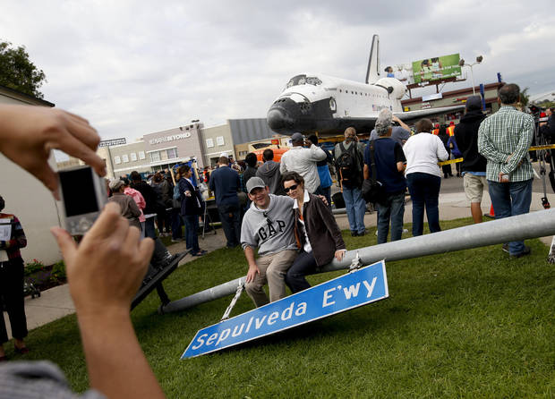 A couple poses with a street sign temporarily removed prior to the transfer of the space shuttle Endeavour in Los Angeles, Friday, Oct. 12, 2012. Endeavour's 12-mile road trip kicked off shortly before midnight Thursday as it moved from its Los Angeles International Airport hangar en route to the California Science Center, its ultimate destination, said Benjamin Scheier of the center. (AP Photo/Jae C. Hong)