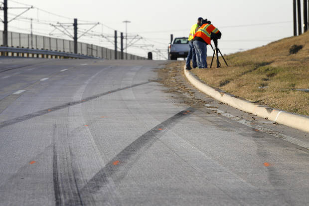 Tire skid marks are seen leaving the road as news cameraman film the area where a single vehicle accident involving Dallas Cowboys player Josh Brent occurred Saturday, Dec. 8, 2012, in Irving, Texas. Brent is facing an intoxication manslaughter charge after a one-vehicle accident that killed linebacker Jerry Brown, a member of the team's practice squad. (AP Photo/Tony Gutierrez)